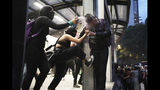 Two women assault a commuter, one spraying him in the face with paint another kicking him, at a bus station, during a protest sparked by a string of alleged sexual attacks by police officers, in Mexico City, Friday, Aug. 16, 2019. On Friday, hundreds of women demonstrated largely peacefully in downtown Mexico City with pink spray paint and smoke. But some protesters trashed the nearby bus station. This week, an auxiliary policeman was held for trial on charges he raped a young female employee at a city museum. (AP Photo/Emilio Espejel)