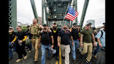 "Members of the Proud Boys and other right-wing demonstrators march across the Hawthorne Bridge during an ""End Domestic Terrorism"" rally in Portland, Ore., on Saturday, Aug. 17, 2019. The group includes organizer Joe Biggs, in green hat, and Proud Boys Chairman Enrique Tarrio, holding megaphone. (AP Photo/Noah Berger)"