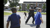 Tulsa Police Officer Donnie Johnson plays with children that live at Savanna Landing apartments Tuesday, July 23, 2019. (Mike Simons/Tulsa World via AP)