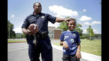 Tulsa Police Officer Donnie Johnson pats Errick Yance, 8, on the head while playing football with him at Savanna Landing apartments Tuesday, July 23, 2019. (Mike Simons/Tulsa World via AP)