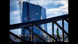 A man stretches as he walks over a bridge in Frankfurt, Germany, Wednesday, Aug. 14, 2019. In the background is the building of the European Central Bank. (AP Photo/Michael Probst)
