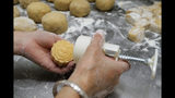 "In this Aug. 9, 2019 photo, a staff member stamps the Chinese words ""Hong Kong people"" on the mooncake at Wah Yee Tang bakery in Hong Kong. This year, a Hong Kong bakery is busy making mooncakes inscribed with wordings related to the recent political movement on the extradition bill. Wah Yee Tang bakery offered pro-protest baked goods stamped with the messages such as ""No withdrawal, no dispersal"", ""Be water"", and ""Hong Kong people"". These political-themed mooncake has attracted people across various district to visit the shop and buy the mooncakes to share with their friends. In the past 12 weeks, Hong Kong has various protests related to the withdrawal of the extradition bill. (AP Photo/Kin Cheung)"