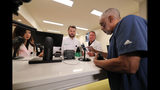 Alex Domino, right, the first ever person to receive medical marijuana in Louisiana, purchases his dose at Capitol Wellness Solutions, in Baton Rouge, La., Tuesday, Aug. 6, 2019. (AP Photo/Gerald Herbert)