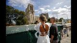 Unos turistas observan la catedral de Notre Dame antes del inicio de una gran descontaminación de plomo en París, el viernes 16 de agosto del 2019. (AP Foto/Francois Mori)