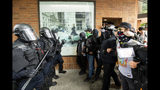 """Police officers face off against protesters opposed to right-wing demonstrators following an """"End Domestic Terrorism"""" rally in Portland, Ore., on Saturday, Aug. 17, 2019. Although the main protest remained largely peaceful, some skirmishes erupted in the following hours and police detained multiple protesters. (AP Photo/Noah Berger)"""