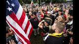 """Members of the Proud Boys and other right-wing demonstrators plant a flag in Tom McCall Waterfront Park during an """"End Domestic Terrorism"""" rally in Portland, Ore., on Saturday, Aug. 17, 2019. Portland Mayor Ted Wheeler said the situation was """"potentially dangerous and volatile"""" but as of early afternoon most of the right-wing groups had left the area via a downtown bridge and police used officers on bikes and in riot gear to keep black clad, helmet and mask-wearing anti-fascist protesters - known as antifa - from following them. (AP Photo/Noah Berger)"""