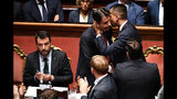 Italian Premier Giuseppe Conte, center, is hugged by Deputy Premier Luigi Di Maio at the end of his address to the Senate as the League's Matteo Salvini sits at left, in Rome, Tuesday, Aug. 20, 2019. Conte on Tuesday announced his resignation, blaming his decision to end his 14-month-old populist government on his rebellious and ambitious deputy prime minister Matteo Salvini. (Ettore Ferrari/ANSA via AP)