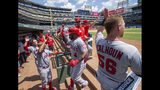 Los Angeles Angels' Luis Rengifo (4) is congratulated in the dugout after hitting a two run home run off of Texas Rangers relief pitcher Phillips Valdez that scored Brian Goodwin during the fifth inning of the first baseball game of a doubleheader Tuesday, Aug. 20, 2019, in Arlington, Texas. (AP Photo/Jeffrey McWhorter)