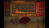 Umbrellas sit in front of an electronic display board at a stock brokerage house in Beijing, Tuesday, Aug. 20, 2019. Asian shares were mostly higher Tuesday after Wall Street rallied on the U.S. decision to give Chinese telecom giant Huawei another 90 days to buy equipment from American suppliers. (AP Photo/Mark Schiefelbein)