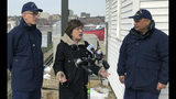FILE - In this Feb. 20, 2019, file photo, Sen. Susan Collins, R-Maine, is flanked by Coast Guard Capt. Brian LeFebvre, left, and Rear Adm. Andrew Tiongson, right, as she addresses reporters after the ribbon-cutting at a U.S. Coast Guard regional command center in South Portland, Maine. National money is already flowing into Maine's 2020 Senate race, offering the latest indicator that incumbent Collins faces a stiff reelection fight. (AP Photo/David Sharp, File)