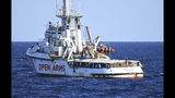 The Open Arms vessel with 107 migrants on board is anchored off the Sicilian vacation and fishing island of Lampedusa, southern Italy, Monday, Aug. 19, 2019. Open Arms on Monday suggested chartering a plane to fly to Spain the migrants blocked off the coast of Italy aboard its boat since early August, to end a stalemate with the Italian Interior minister Matteo Salvini, who won't let private rescue boats into his nation's ports. (AP Photo/Salvatore Cavalli)