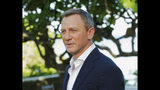 """FILE - In this April 25, 2019, file photo, actor Daniel Craig poses for photographers during the photo call of the latest installment of the James Bond film franchise, currently known as """"Bond 25,"""" in Oracabessa, Jamaica. The 25th James Bond movie has a title: """"No Time to Die."""" Film producers announced the moniker Tuesday, Aug. 20, for the film that has long been referred to simply as """"Bond 25."""" """"No Time to Die"""" returns Daniel Craig to the role of 007, along with returning cast members Lea Seydoux, Naomie Harris, Ben Whishaw and Ralph Fiennes. Rami Malek plays the villain. (AP Photo/Leo Hudson, File)"""