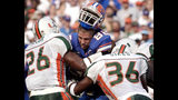 FILE - In this Sept. 7, 2002 file photo, Florida's tight end Aaron Walker, (82) loses his helmet as he is hit by Miami defenders Sean Taylor (26) and Maurice Sikes (36) during the first quarter of a NCAA college football game, in Gainesville, Fla. The Florida-Miami series has been one-sided of late. The Hurricanes have won seven of the last eight and 12 of 16. But the teams separated by 300 miles have provided several instant classics and plenty of hard feelings over the previous 80 years. (AP Photo/Phelan Ebenhack, File)