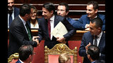 """Italian Premier Giuseppe Conte, center, greets Deputy Premier and Interior Minister Matteo Salvini, as he arrive to address the Senate, in Rome, Tuesday, Aug. 20, 2019. Italian Premier Conte blasted the League's leader Salvini for his decision to spark a government crisis that risks triggering """"a spiral of political and financial instability."""" (Ettore Ferrari/ANSA via AP)"""