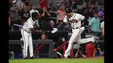Atlanta Braves' Freddie Freeman rounds third base as coach Ron Washington, left, congratulates him on his a home run over left field during the fourth inning of a baseball game against the Miami Marlins, Tuesday, Aug. 20, 2019, in Atlanta. (AP Photo/John Amis)