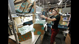 FILE - In this March 12, 2019, file photo, Yakaranday Arce packs sold clothing for shipment at the ThredUp sorting facility in Phoenix. J.C. Penney and Macy's are in the midst of rolling out a few dozen ThredUp branded shops each in time for the back-to-school shopping season. The partnerships follow a similar deal with department store retailer Stage Stores. (AP Photo/Matt York, File)