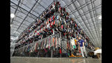 FILE - In this March 12, 2019, file photo thousands of garments are stored on a three-tiered conveyor system at the ThredUp sorting facility in Phoenix. J.C. Penney and Macy's are in the midst of rolling out a few dozen ThredUp branded shops each in time for the back-to-school shopping season. The partnerships follow a similar deal with department store retailer Stage Stores. (AP Photo/Matt York, File)