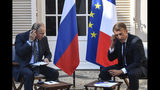 French President Emmanuel Macron, right, and Russian President Vladimir Putin adjust their earphones at the fort of Bregancon in Bormes-les-Mimosas, southern France, Monday Aug. 19, 2019. French President Emmanuel Macron and Russian President Vladimir Putin are meeting to discuss the world's major crises, including Ukraine, Iran and Syria, and try to improve Moscow's relations with the European Union. (Gerard Julien, Pool via AP)