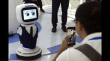 In this July 23, 2019, photo, a man takes photos with his cellphone of a Siasun greeting robot in a demonstration hall of Siasun Robot and Automation in Shenyang in northeastern China's Liaoning Province. From Thailand to Kenya, trains run on tracks from steel mills in China's northeast, a rust-belt region that is trying to capitalize on a multibillion-dollar national initiative to build ports, railways and other projects abroad. Announced in 2012, the Belt and Road Initiative is helping to boost demand from developing countries at a time when the domestic economy is slowing and exporters face U.S. tariff hikes in a war over trade and technology.(AP Photo/Olivia Zhang)