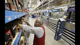 FILE - In this Feb. 23, 2018, file photo sales associate Larry Wardford, of Holliston, Mass., places items on selves at a Lowe's retail home improvement and appliance store, in Framingham, Mass. Lowe's Companies, Inc. reports financial results Wednesday, Aug. 21, 2019. (AP Photo/Steven Senne, File)