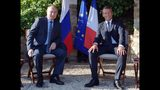 Russian President Vladimir Putin, left, and French President Emmanuel Macron pose for a photo during their meeting at the fort of Bregancon in Bormes-les-Mimosas, southern France, Monday Aug. 19, 2019. French President Emmanuel Macron and Russian President Vladimir Putin are meeting to discuss the world's major crises, including Ukraine, Iran and Syria, and try to improve Moscow's relations with the European Union. (Alexei Druzhinin, Sputnik, Kremlin Pool Photo via AP)