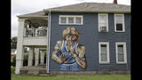 """A mural of former NBA star Larry Bird is seen on the side of a multi-family residence in Fountain Square, Wednesday, Aug. 21, 2019, in Indianapolis. Larry Bird likes the mural but not the tatts. Bird's attorney, Gary Sallee, says the former Indiana Pacers executive """"needs to protect"""" his brand and """"doesn't want to be seen as a tattooed guy."""" Artist Jules Muck says she was just trying to be funny. The mural is a replica of Bird's appearance on a 1977 Sports Illustrated cover when he played college ball for Indiana State. (AP Photo/Darron Cummings)"""