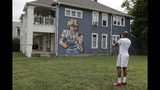 """D'Andre Peyton takes a photo of a mural of former NBA star Larry Bird on the side of a multi-family residence in Fountain Square, Wednesday, Aug. 21, 2019, in Indianapolis. Larry Bird likes the mural but not the tatts. Bird's attorney, Gary Sallee, says the former Indiana Pacers executive """"needs to protect"""" his brand and """"doesn't want to be seen as a tattooed guy."""" Artist Jules Muck says she was just trying to be funny. The mural is a replica of Bird's appearance on a 1977 Sports Illustrated cover when he played college ball for Indiana State. (AP Photo/Darron Cummings)"""