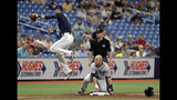 Seattle Mariners' Kyle Seager, lower right, slides into third base safely as Tampa Bay Rays' Matt Duffy fields a wild throw on a single by Omar Narvaez during the fourth inning of a baseball game Wednesday, Aug. 21, 2019, in St. Petersburg, Fla. Looking on is umpire D.J. Reyburn. (AP Photo/Chris O'Meara)