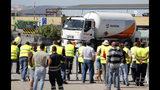 Foto de archivo del lunes 12 de agosto de 2019, que muestra a conductores de camiones cisterna en huelga observando a un compañero conductor mientras sale de un depósito de combustible en Aveiras, en las afueras de Lisboa. (Foto AP/Armando Franca, Archivo)