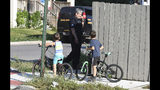 Two boys watch as a Detroit police officer investigates a fatal dog attack on a young girl who later died of her injuries in Detroit on Monday, Aug. 19, 2019. Police say the owner of three dogs is in custody after the animals killed Emma Hernandez, 9, as she rode a bike. The girl's father, Armando Hernandez, says the man was warned that a fence was too flimsy to hold the dogs. (Max Ortiz/Detroit News via AP)