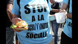 "An activist wearing a sweeter reading ""Stop discrimination"" holds a home-made hamburger during a demonstration outside of a McDonald's restaurant, Thursday, Aug. 22, 2019 in Hendaye, southwestern France. The G-7 summit has for the first time co-opted the message of its protesters: Capitalism has led to damaging inequality, hurting the environment also harms the global economy, and a handful of rich countries can't be the only ones making decisions for the world. (AP Photo/Bob Edme)"