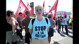 "French activist Adele Lepoutre wears a sweeter reading ""Stop discrimination"" during a demonstration outside of a McDonald's restaurant, Thursday, Aug. 22, 2019 in Hendaye, southwestern France. The G-7 summit has for the first time co-opted the message of its protesters: Capitalism has led to damaging inequality, hurting the environment also harms the global economy, and a handful of rich countries can't be the only ones making decisions for the world. (AP Photo/Bob Edme)"