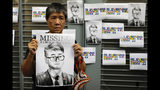 A supporter holds a poster outside of the British Consulate in Hong Kong during a rally in support of an employee of the consulate who was detained while returning from a trip to China, Wednesday, Aug. 21, 2019. China said Wednesday a staffer at the British consulate in Hong Kong has been given 15 days of administrative detention in the city of Shenzhen for violating a law on public order. (AP Photo/Vincent Yu)