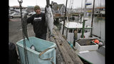 In this photo taken Monday, July 22, 2019, Ivan Montoya, left, of Flannery Seafood, holds up chinook salmon after it was brought in by Ron Kemp, right, at Fisherman's Wharf in San Francisco. California fishermen are reporting one of the best salmon fishing seasons in more than a decade, thanks to heavy rain and snow that ended the state's historic drought. It's a sharp reversal for chinook salmon, also known as king salmon, an iconic fish that helps sustain many Pacific Coast fishing communities.(AP Photo/Eric Risberg)