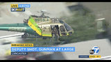 This photo taken from video provided by KABC-TV shows a sheriff's department helicopter with a sniper in an open door searching for a gunman at large in Lancaster, Calif. on Wednesday, Aug. 21, 2019. The mayor of Lancaster says a deputy shot and wounded outside a Los Angeles County sheriff's station is going to be okay after visiting him in the hospital. Authorities are searching for the shooter in buildings surrounding the station where the deputy was hit in the shoulder while standing in the parking lot Wednesday afternoon. (KABC-TV via AP)