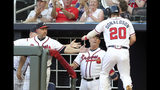 Atlanta Braves' Josh Donaldson (20) is greeted at the dugout by coach Walt Weiss, left, and manger Brian Snitker, center, after scoring on a hit during the second inning of a baseball game against the Miami Marlins, Thursday, Aug. 22, 2019, in Atlanta. (AP Photo/Tami Chappell)