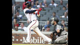 Atlanta Braves' Adeiny Hechavarria, left, singles in a run as Miami Marlins catcher Bryan Holiday looks on during the second inning of a baseball game Thursday, Aug. 22, 2019, in Atlanta. (AP Photo/Tami Chappell)