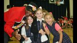 """In this October 2016 picture provided by the Orleans Parish Sheriff's Office longtime aerobatic pilot Franklin Augustus dressed in his """"Drug Fighter"""" superhero costume poses with students at a program for school children put on by Sheriff Marlin Gusman. Augustus died Aug. 16, 2019,2019, when the small plane he was piloting crashed shortly after taking off from New Orleans' Lakefront Airport. Popular television anchor Nancy Parker, who was working on a story about Augustus also died in the crash. (Orleans Parish Sheriff's Office via AP)"""