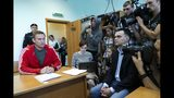 Russian opposition leader Alexei Navalny, left, speaks to the media prior to a court session in Moscow, Russia, Thursday, Aug. 22, 2019. A Moscow court has rejected an attempt to prolong the jail sentence of opposition leader Alexei Navalny, clearing the way for him to be released on Friday morning. Navalny, the Kremlin's most prominent foe, was sentenced last month to 30 days for calling on people to take part in an unauthorized protest. (AP Photo/Alexander Zemlianichenko)