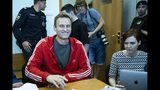 Russian leader Alexei Navalny, center, smiles as he speaks to the media prior to a court session in Moscow, Russia, Thursday, Aug. 22, 2019. Navalny is due in court, where a judge will consider extending his detention in lieu of days spent in hospital, where he was being treated for an allergic attack at the end of July. Navalny was due to be released on Friday after serving 30 days for calling an unsanctioned protest. (AP Photo/Alexander Zemlianichenko)