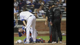 New York Mets starting pitcher Jacob deGrom, top left, checks on catcher Tomas Nido, who was hit by the bat of Atlanta Braves' Josh Donaldson (20) during the sixth inning of a baseball game Friday, Aug. 23, 2019, in New York. (AP Photo/Mary Altaffer)