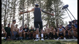 In this Thursday, Aug. 22, 2019, photo, former Paradise High School football player Jeff Maehl, who played in the NFL, talks to the team after practice in Paradise, Calif. Paradise's game against Williams High School on Friday will be the first game for the team since a wildfire nearly destroyed the foothill community last year. (AP Photo/Rich Pedroncelli)