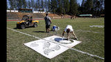 In this Thursday, Aug. 22, 2019, photo, Paul Orlando, right, the defensive coordinator for the Paradise High School football team, paints the numbers on the field in preparation for the teams first game of the season in Paradise, Calif. Paradise's game against Williams High School Friday night, Aug. 23, will be the first game for the team since a wildfire nearly destroyed the foothill community last year. (AP Photo/Rich Pedroncelli)