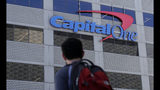 FILE - In this July 16, 2019, file photo, a man walks across the street from a Capital One location in San Francisco. Federal prosecutors say Paige Thompson, the woman accused of hacking Capital One and at least 30 other organizations, is a threat to herself and society, a flight risk and should be kept locked up until her trial. Prosecutors are expected to make their argument for detaining Thompson at a hearing Friday, Aug. 23 in Seattle. Prosecutors say the former software engineer has a history of stalking and threatening to kill people and to get herself killed by police. Her lawyers denied that she is violent. (AP Photo/Jeff Chiu, File)