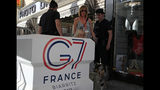 A woman with her family walks past police officers inside the restricted area ahead of the G-7 summit in Biarritz, France Friday, Aug. 23, 2019. U.S. President Donald Trump will join host French President Emmanuel Macron and the leaders of Britain, Germany, Japan, Canada and Italy for the annual G-7 summit in the elegant resort town of Biarritz. (AP Photo/Peter Dejong)