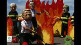 """Un hombre con máscara del presidente estadounidense Donald Trump y otros """"líderes mundiales"""" participan de una protesta en vísperas de la cumbre del G7 en Biarritz, Francia, viernes 23 de agosto de 2019. (AP Foto/Peter Dejong)"""
