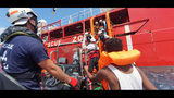 """Rescued migrants are helped boarding the Ocean Viking ship, operated by the NGOs Sos Mediterranee and Doctors Without Borders, in the Mediterranean Sea, Tuesday, Aug. 13, 2019. More than 500 rescued migrants are stuck in the Mediterranean on two NGO boats, as Italy and Malta continue to deny them access to their ports. French charity group Doctors Without Borders (MSF) said late Monday in a tweet that it had completed """"a critical rescue"""" of another 105 people onto the Ocean Viking, raising the total number of migrants on board ship to 356. (Hannah Wallace Bowman/MSF/SOS Mediterranee via AP)"""