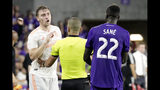 Referee Nima Saghafi, center, separates Atlanta United's Julian Gressel, left, and Orlando City's Lamine Sane (22) as they get in an argument during the final moments of an MLS soccer match Friday, Aug. 23, 2019, in Orlando, Fla. (AP Photo/John Raoux)