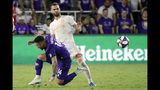 Orlando City's Dom Dwyer (14) falls as he collides with Atlanta United's Leandro Gonzalez Pirez while going for the ball during the second half of an MLS soccer match Friday, Aug. 23, 2019, in Orlando, Fla. (AP Photo/John Raoux)