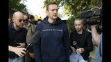 Russian opposition leader Alexei Navalny speaks to the media as he leaves a detention center after he was released, in Moscow, Russia, Friday, Aug. 23, 2019. Navalny, the Kremlin's most prominent foe, was sentenced last month to 30 days for calling on people to take part in an unauthorized protest. (AP Photo/Dmitry Serebryakov)